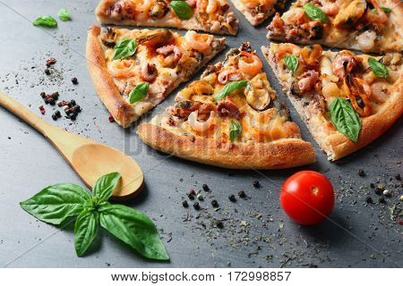 Tasty sliced pizza with seafood and tomato on grey background