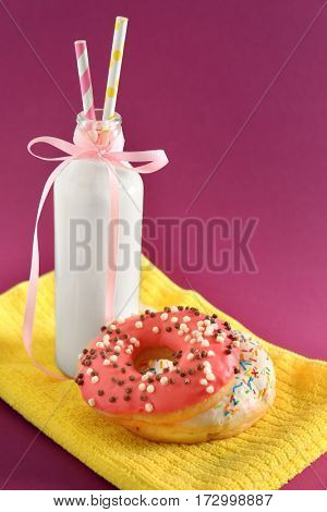 Delicious donuts and bottle of milk on color background