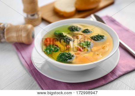 Bowl with vegetable soup on pink napkin