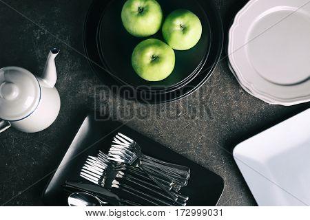 Set of dinnerware with apples on dark table