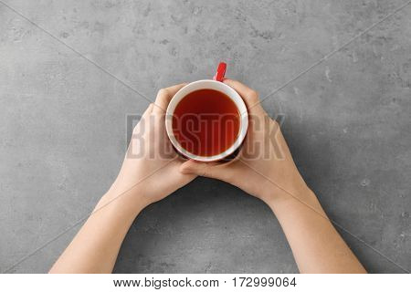 Female hands holding cup of aromatic tea on grey background