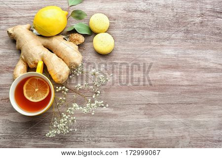 Cup of tea with lemon, ginger and macaroons on wooden background