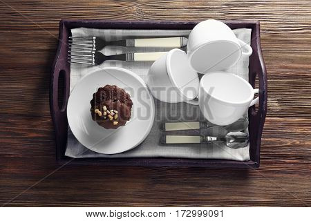Cups set with tasty chocolate cake, on wooden tray