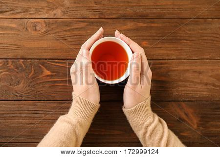 Female hands holding cup of aromatic tea on wooden background
