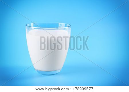 Glass of milk on blue background