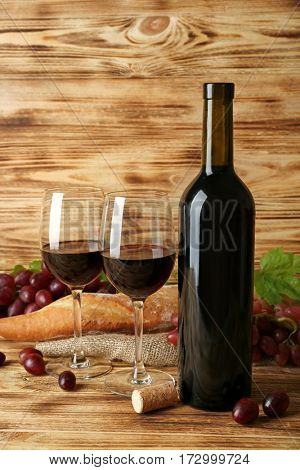 Wine, baguette and red grape on wooden background
