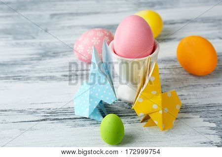 Easter bunnies with colorful eggs on wooden table