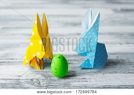 Easter bunnies with colorful egg on wooden table