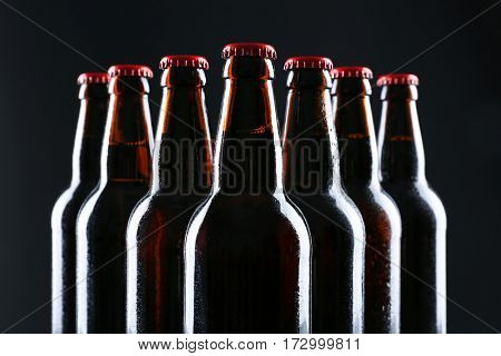 Bottles of beer on black background, closeup