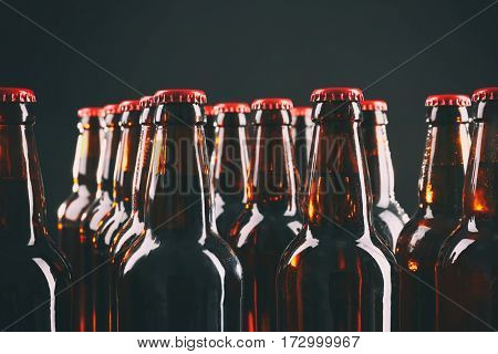 Bottles of beer on black background, closeup