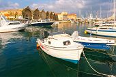 Chania Arsenals, the Venetian shipyards, and fishing boats in old harbour of Chania with Lighthouse in cloudy summer morning, Crete, Greece poster