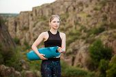 Young sportive girl smiling, holding yogamat, standing on rock in canyon. Copy space. poster