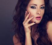Fashionable bright makeup woman with long hair creative manicured nails and grey eyeshadow with black eye liner looking sexy. Closeup toned portrait. Perfect eyebrow and pink lipstick poster