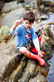 Young boy thrilled at finding a live snail in a rockpool by the seaside in summer. poster