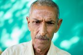 Real Cuban people and emotions portrait of sad old latino man from Havana Cuba looking down with worried face and depressed expression poster