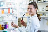 Portrait of pharmacist holding a medicine bottle in pharmacy poster