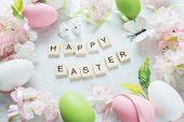 """Beautiful delicate Easter composition with pink cherry flowers multicolored Easter eggs Easter bunny butterfly and inscription """"Happy Easter"""" on the stone background poster"""