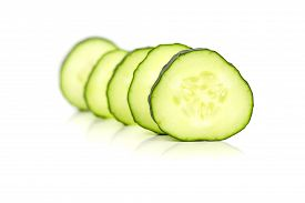 Closeup image of cucumber slices, over a white background.