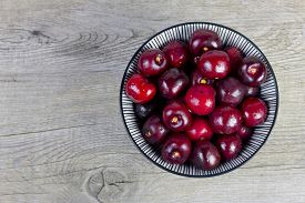 Cherries in a bowl on a wooden surface.