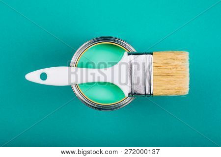 Brush With White Handle On Open Can With Turquoise Color Of Paint On Blue Background. Renovation Con