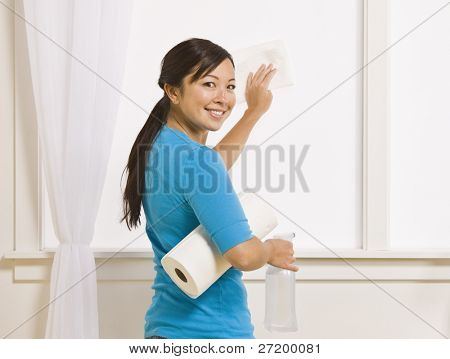 An attractive asian young female washing a window. She is holding a roll of paper towels and has her head turned to smile toward the camera. Horizontally framed photo.