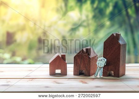 Small House With Key Placed On Wooden Table On Natural Background.concept For Property Ladder, Mortg