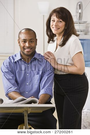 A young man is seated in an office and an older woman is standing next to him with her arms on his shoulder.  They are smiling at the camera.  Vertically framed shot.