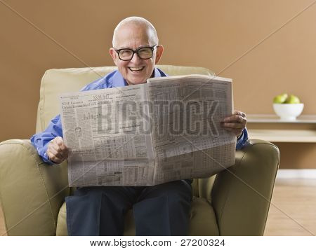 An elderly man is sitting in his living room reading a newspaper.  He is smiling at the camera.  Horizontally framed shot.