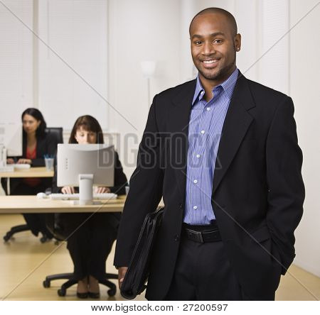 A young businessman is standing in an office with some other business people.  He is smiling at the camera.  Horizontally framed shot.