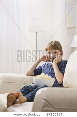 A young girl is seated on the living room sofa with a bowl of popcorn and is talking on a cell phone.  She is smiling at the camera.  Vertically framed shot.