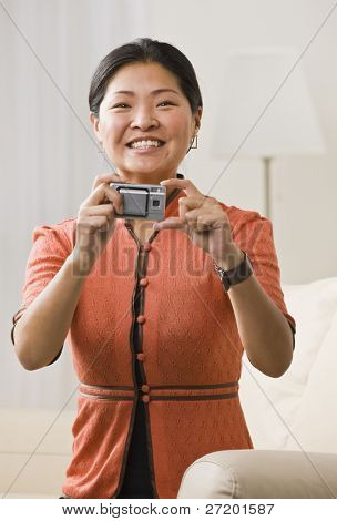 A woman is holding a camera in her hands.  She is smiling at the camera.  Vertically framed shot.