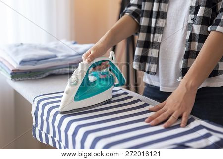 Detail Of Female Hands Holding The Iron, Ironing Washed, Wrinkled Clothes On The Ironing Board. Sele