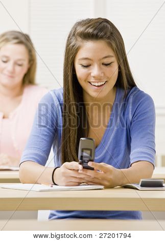 Student text messaging on cell phone in classroom