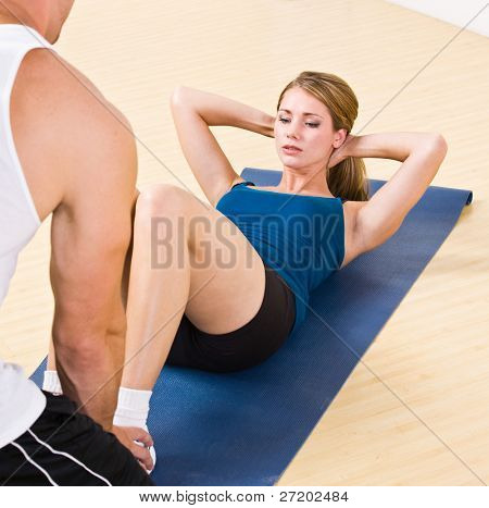 Trainer helping woman do sit ups