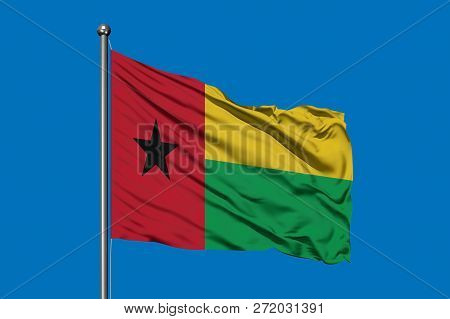 Flag Of Guinea Bissau Waving In The Wind Against Deep Blue Sky. Guinean Flag.