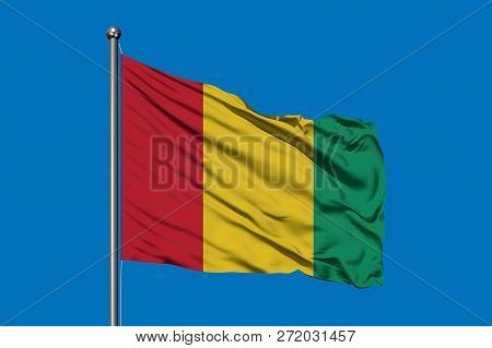 Flag Of Guinea Waving In The Wind Against Deep Blue Sky. Guinean Flag.