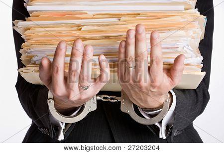 Businessman in handcuffs holding file folders
