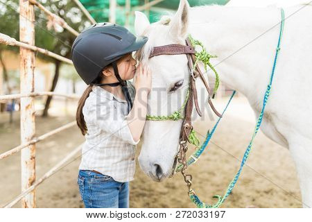 Loving Cute Girl Kissing White Horse On Head While Standing At Ranch