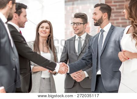 business team looks at the handshake of business partners