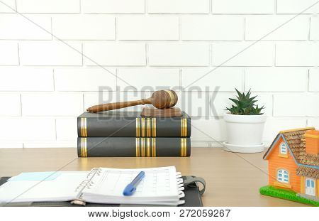 Judge Gavel Law Book & Home House Model On Wooden Desk Near White Brick Wall. Real Estate Dispute &