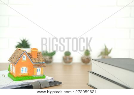 Book & House Model On Wooden Desk. Realtor Real Estate Agent Workplace. Buying Selling & Renting Pro