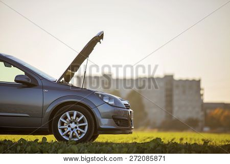 Side View Detail Of Car With Open Hood On Empty Gravel Field Road On Blurred Apartment Building And