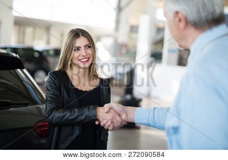 Woman giving an handshake to seal the deal for her new car