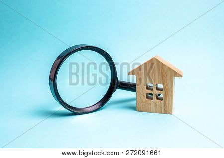 Wooden House And Magnifying Glass On A Blue Background. Buying And Selling Real Estate, Building New