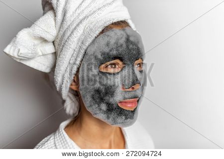 Face mask foam bubbles charcoal detox facial treatment at home -asian girl purifying skin removing dead skin cells with chemical peel korean face sheet in bathroom. poster