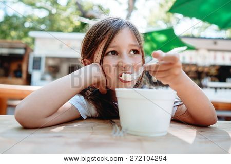 Little Girl Eating Ice Cream At A Cafe