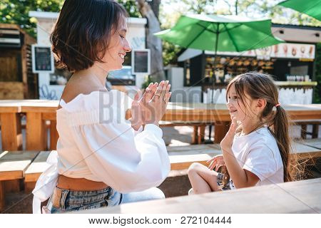 Mother And Daughter Are Sitting In A Cafe