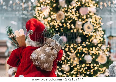 Santa From Behind With Gift Bag On Background Of Bokeh Christmas Tree.