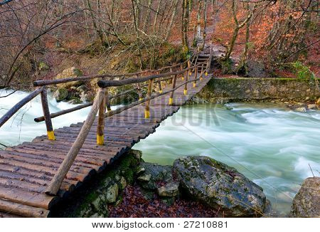 Wooden bridge over mountain river