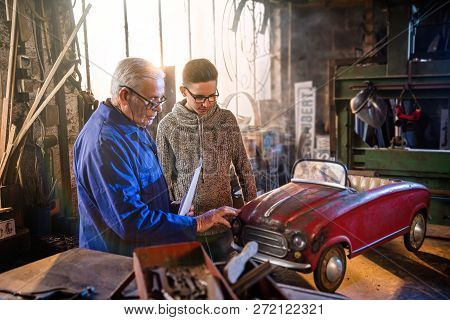 A grandfather and his grandson restoring an old pedal car poster